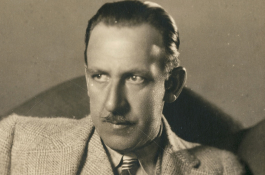 An old image of Tod Browning circa 1920s-30s, film director. Browning wears a suit and has a small, finely styled moustache, his hair combed back.